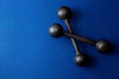 Retro iron grunge dumbbells on blue yoga mat background stock photo