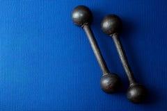 Retro iron grunge dumbbells on blue yoga mat background Royalty Free Stock Photos