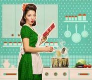 Retro jonge vrouw het koken spaghettei en binnen het lezen van receptenboek Stock Foto's