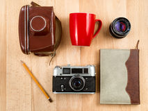 Retro journalist workspace with camera, lens, notebook, pencil a Royalty Free Stock Photo