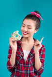 Retro joyful woman enjoy sweets, dessert standing over blue back Stock Photography