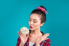 Retro joyful woman enjoy sweets, dessert standing over blue back Stock Photography