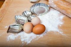 Retro julkakaskärare med ägg och mjöl på träbräde Fotografering för Bildbyråer