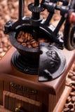 Retro- Kaffeemühle auf dem unscharfen Hintergrund von Kaffeebohnen Nahaufnahme Lizenzfreie Stockfotografie