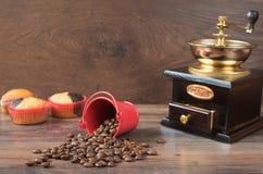 Retro- Kaffeemühle, Kaffeemühle-Kaffeetasse, Schokoladenkleiner kuchen, Muffins, Kaffeebohnen Hölzernes backg Stockfotografie