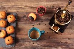 Retro- Kaffeemühle, Kaffeemühle-Kaffeetasse, Schokoladenkleiner kuchen, Muffins, Kaffeebohnen Hölzernes backg Lizenzfreie Stockbilder