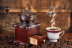 Retro- Kaffeemühle und Schale mit dem schwarzen Kaffee, der auf hölzernem Hintergrund raucht Lizenzfreie Stockfotografie