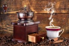 Retro- Kaffeemühle und Schale mit dem schwarzen Kaffee, der auf hölzernem Hintergrund raucht Lizenzfreies Stockbild