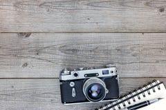 Retro kamera, anteckningsbok och penna på den gråa trätabellen Royaltyfria Foton