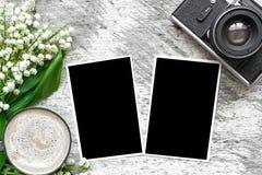 Retro- Kamera der Weinlese mit den leeren Fotorahmen, zum Ihrer Bilder und Kaffeetasse mit Maiglöckchen zu setzen blüht Lizenzfreies Stockfoto