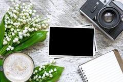 Retro kamera för tappning med tomma fotoramar som sätter din bilder, tomma anteckningsbok och kaffekopp med blommor Royaltyfri Fotografi