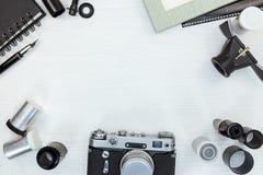 Retro kamera, filmrullar, lins, tom fotoram på vit woode royaltyfri foto