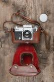Retro kamera i läderfall på träbakgrund Arkivbilder