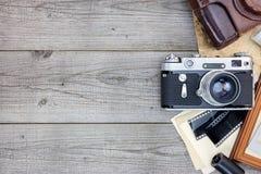 Retro kamera, negativa filmer och fotoram på gammalt träbräde Arkivbild