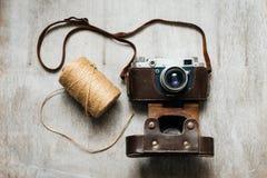 Retro kamera och en skein av tråden på träbakgrund Fotografering för Bildbyråer
