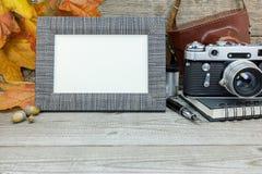 Retro kamera- och fotoram på grå träbakgrund med nedgången Royaltyfri Bild
