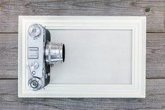 Retro kamera och tom vit fotoram på trätabellbackgro Royaltyfria Bilder