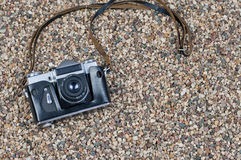Retro kamera på en stenig strand Arkivfoto