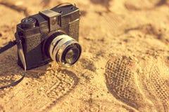 Retro kamera på sanden Arkivbild