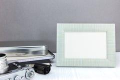 Retro kamera, rulle för negativ film och tom fotoram på grå färger b arkivfoton