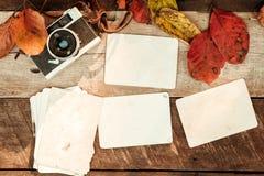 Retro- Kamera und leeres altes sofortiges Papierfotoalbum auf hölzerner Tabelle mit Ahornblättern in der Herbstgrenze entwerfen Lizenzfreies Stockfoto