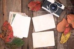 Retro- Kamera und leeres altes sofortiges Papierfotoalbum auf hölzerner Tabelle mit Ahornblättern in der Herbstgrenze entwerfen Stockbild