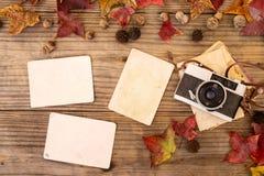 Retro- Kamera und leeres altes sofortiges Papierfotoalbum auf hölzerner Tabelle mit Ahornblättern im Herbst Stockfotografie