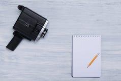 Retro kamera wideo na świetle - szary biurko z prześcieradłem w kratkę papier i prosty ołówek z przestrzenią dla nagrywać, fotografia royalty free