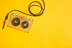 Retro kasety taśma i audio dźwigarka na żółtym tle kosmos kopii obrazy stock