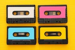 Retro kasety taśmy kolekcja nad żółtym drewnianym stołem Odgórny widok kosmos kopii obrazy royalty free