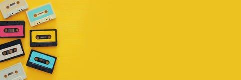Retro kasety taśmy kolekcja nad żółtym drewnianym stołem Odgórny widok kosmos kopii Zdjęcia Royalty Free