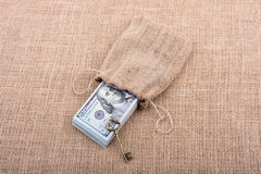 Retro key and bundle of US dollar in a sack Stock Photos