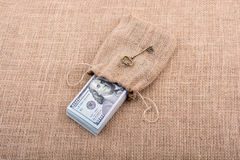 Retro key and bundle of US dollar in a sack Royalty Free Stock Photography