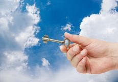 Retro key in hand on blue sky Stock Images