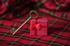 Retro key and little red gift on a tablecloth. Stock Photo