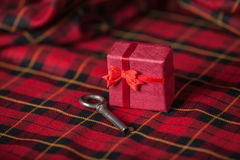 Retro key and little red gift on a tablecloth. Royalty Free Stock Photography