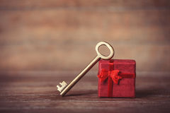 Retro key and little red gift. On wooden table. Photo in old color image style Royalty Free Stock Photo