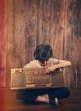 Retro- Kind, das auf Stereomusik-Spieler hört stockbilder