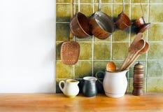 Retro kitchen still life interior. Brass utensils, chef accessories. Hanging copper kitchenware set. Pots, stewpots. Coffee maker, spoon, skimmer. Different Stock Photo