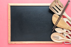 Retro kitchen utensils with empty blackboard on pink background. Stock Photography