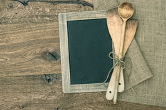 Retro kitchen utensils and vintage blackboard on wooden backgrou Stock Images