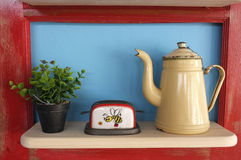 Retro kitchenware and plant pot on wooden shelf Stock Photography