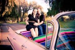 Retro klädda par i rosa Cadillac Arkivbild