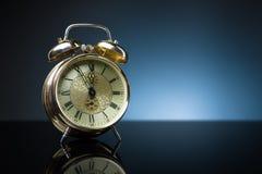 Retro klocka, fem till tolv, blå bakgrund Royaltyfri Bild