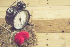Retro klocka med förälskelsehjärtagarn på den wood pinnen på wood bakgrund Arkivbilder