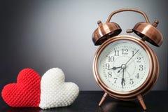Retro klocka med förälskelsehjärtagarn på svart bakgrund - tid av l Arkivbild