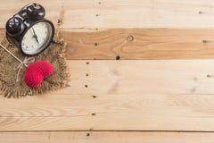 Retro klocka med förälskelsehjärtagarn på wood bakgrund Arkivbild