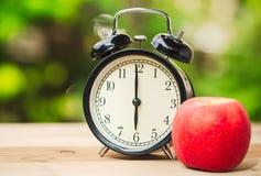 Retro klocka med morgonfruktäpplet Arkivfoto