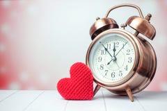 Retro klocka med rött hjärtagarn för förälskelse på rosa bakgrund Royaltyfri Bild