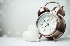 Retro klocka med vitt hjärtagarn för förälskelse på grå bakgrund Arkivbilder